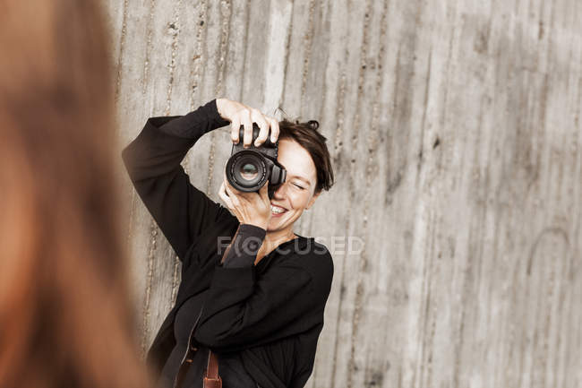 Happy woman photographing friend — Stock Photo