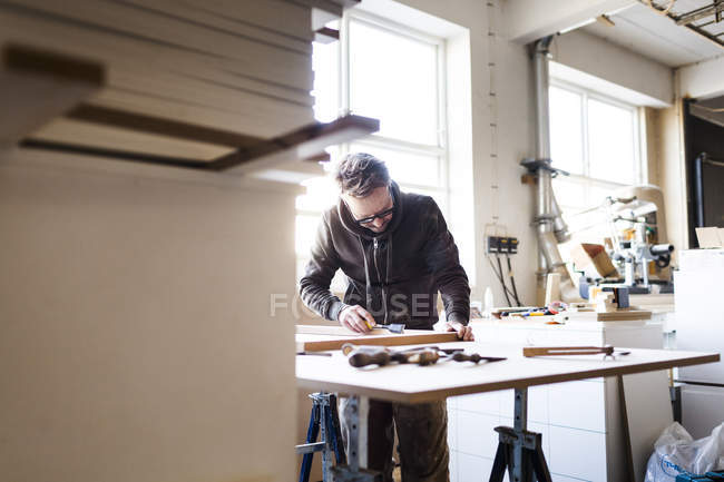 Carpenter using chisel at table — Stock Photo