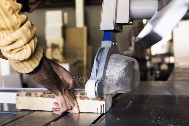 Плотник резки древесины с помощью пилы — стоковое фото
