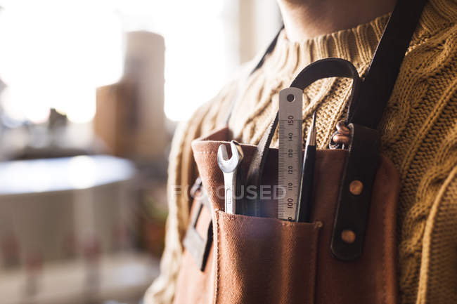 Carpenter with work tools in apron pocket — Stock Photo