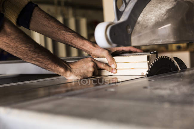 Carpenter cutting wood using table saw — Stock Photo