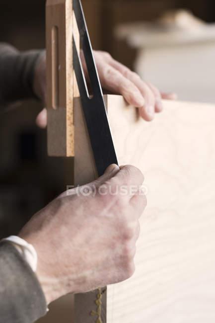 Carpenters hands measuring wood — Stock Photo