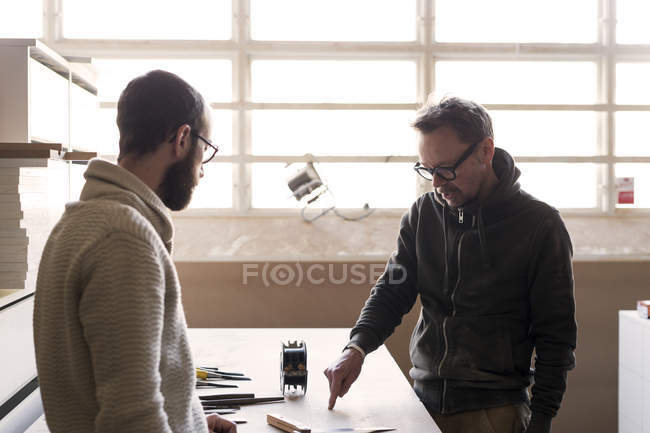 Carpenter talking to client in workshop — Stock Photo