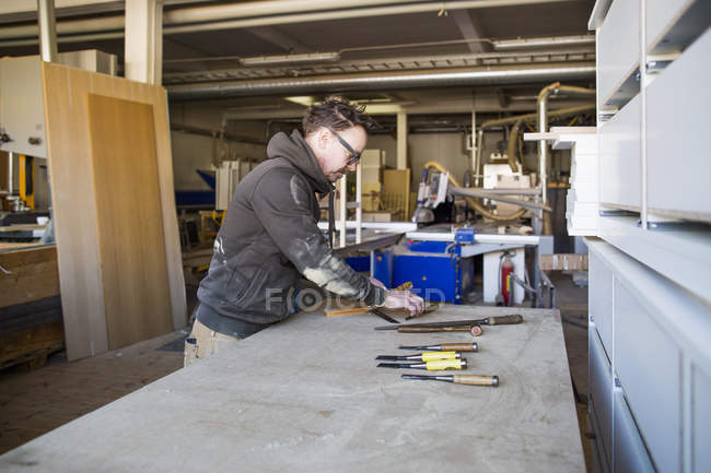 Carpenter with tools at table — Stock Photo