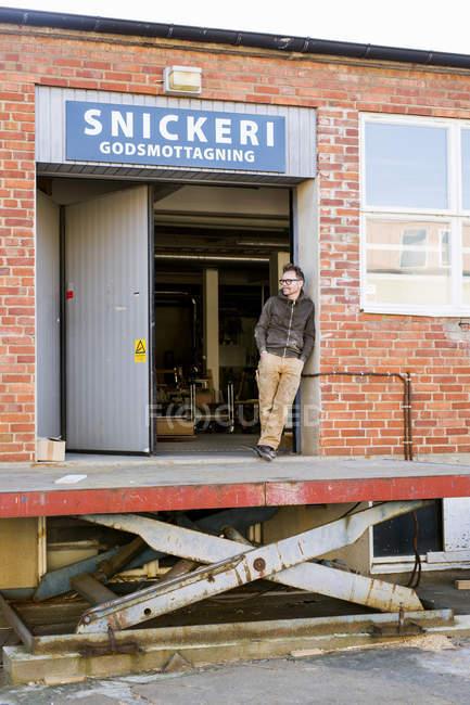 Apoyado en la puerta del taller de carpintero - foto de stock