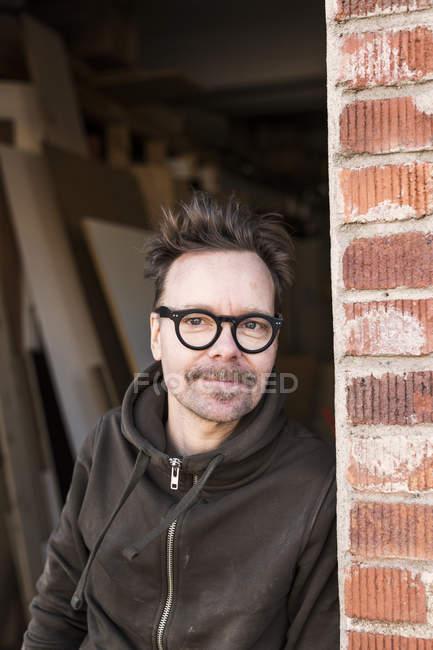 Карпентер, спираючись на цегляна стіна — стокове фото