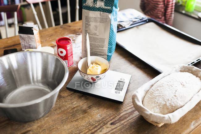 Pack of flour and dough loaf on table — Stock Photo