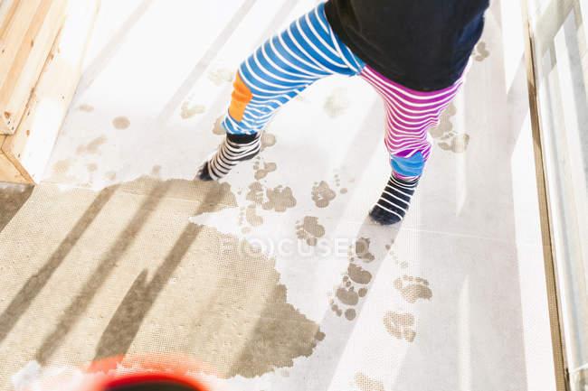 Chico pisando harina en el suelo - foto de stock