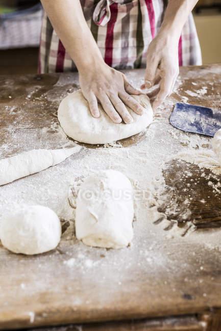 Mãos de padeiros, amassar massa de pão na mesa — Fotografia de Stock