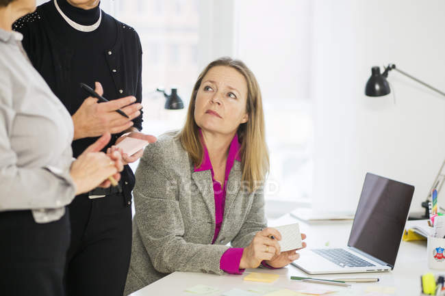 Businesswoman looking at colleagues — Stock Photo