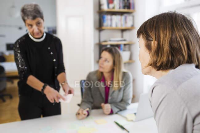 Empresárias, comunicando-se em mesa de escritório — Fotografia de Stock