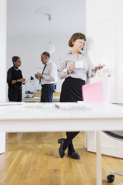 Mulher de negócios com telefone e colegas discutindo — Fotografia de Stock
