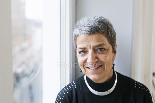 Geschäftsfrau sitzt auf Fensterbank — Stockfoto