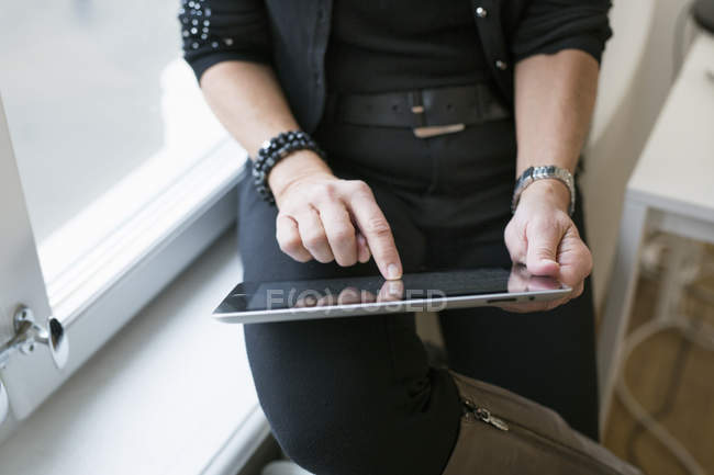 Businesswoman using tablet and sitting on windowsill — Stock Photo
