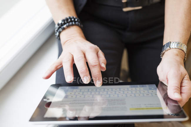 Woman using tablet and sitting on windowsill — Stockfoto