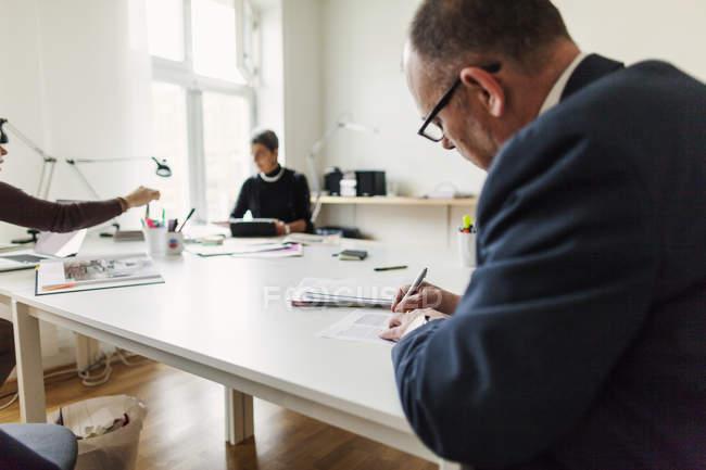 Бизнесмен подписывает контракт, пока деловые женщины работают — стоковое фото