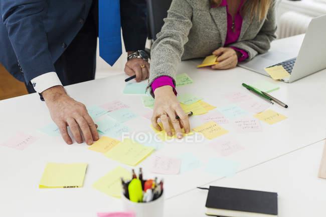 Business people preparing reminders at desk — Stock Photo