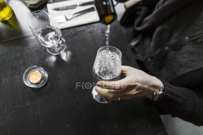 Man pouring water in wine glass — Stock Photo