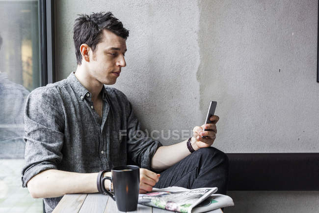 Человек, используя мобильный телефон в кафе — стоковое фото