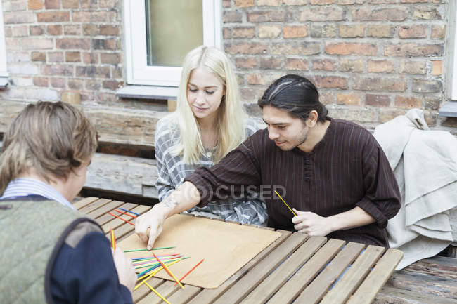 Friends playing Mikado at cafe — Stock Photo