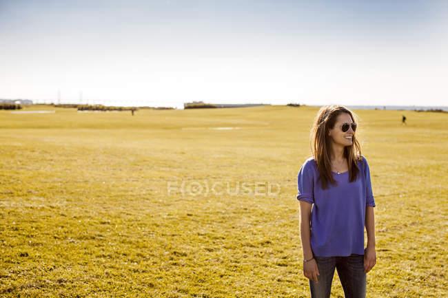 Счастливая женщина стоит в парке — стоковое фото