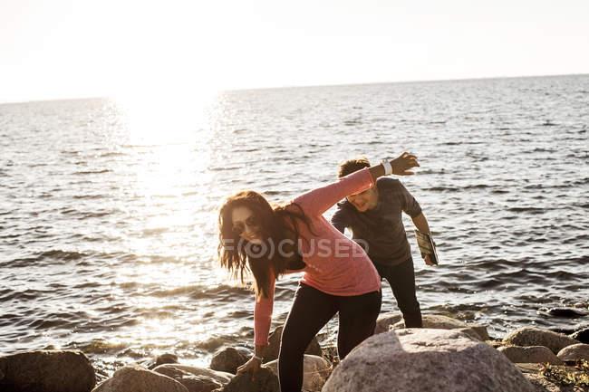 Juguetona pareja joven caminando sobre rocas - foto de stock