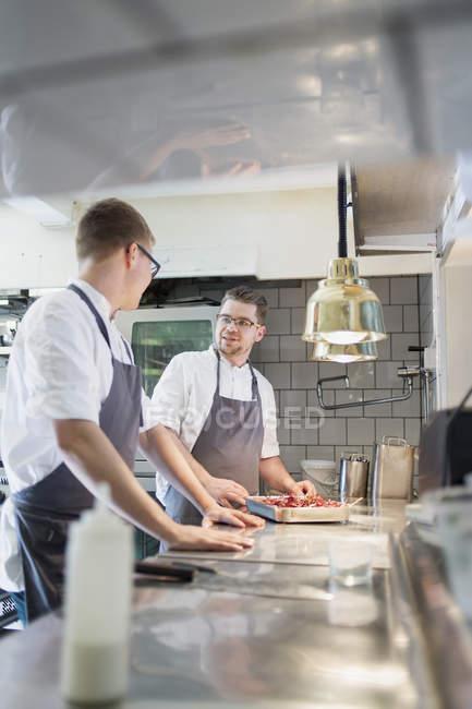 Шеф-кухарі спілкування в комерційний кухня — стокове фото