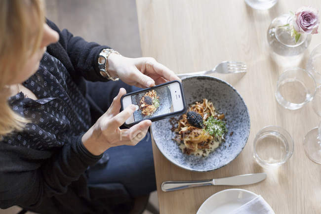 Женщина фотографирует еду — стоковое фото