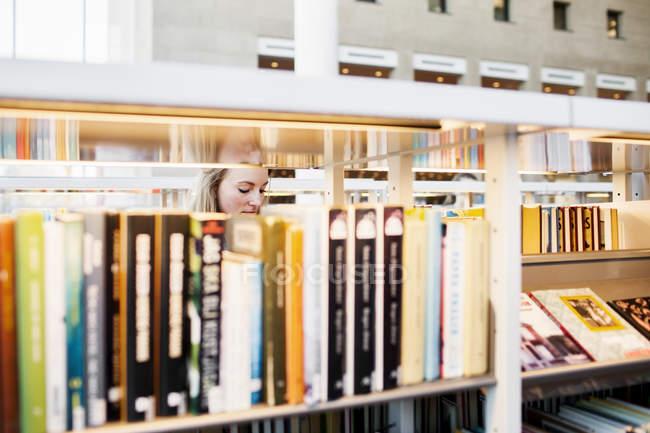 Estudiante a través de libros - foto de stock