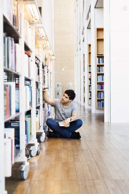 Young man sitting choosing book — Stock Photo