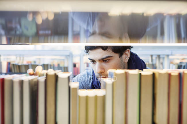 Serious young man choosing book — Stock Photo