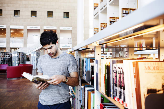 Молодий чоловік читає книжки в бібліотеці. — стокове фото