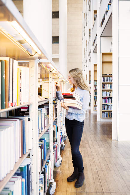 Mujer joven elegir libros - foto de stock