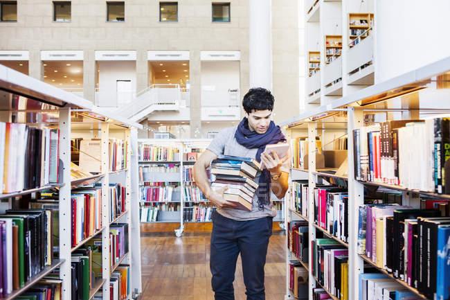 Jeune homme sélection de livres de bibliothèque — Photo de stock