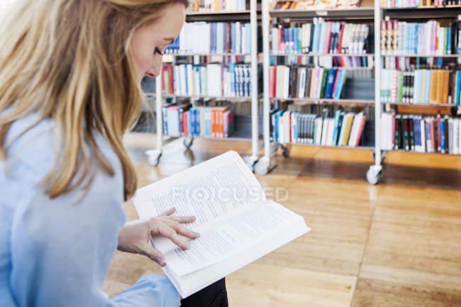 Libro de lectura de mujer joven - foto de stock