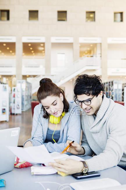 Homem leitura documento com amigo — Fotografia de Stock