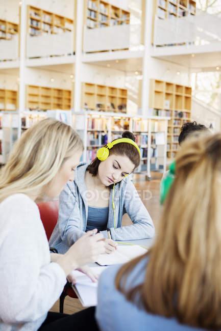 Donna con amici in biblioteca — Foto stock