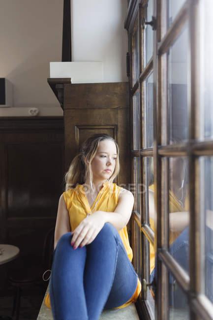 Giovane donna seduta sul davanzale della finestra — Foto stock