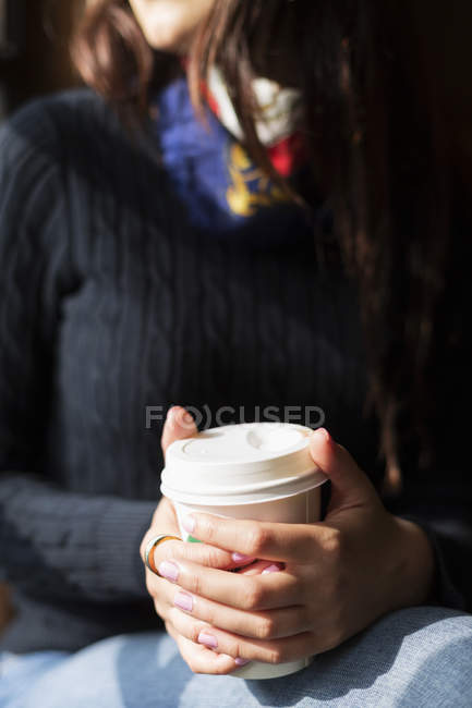 Young woman holding disposable coffee — Stock Photo