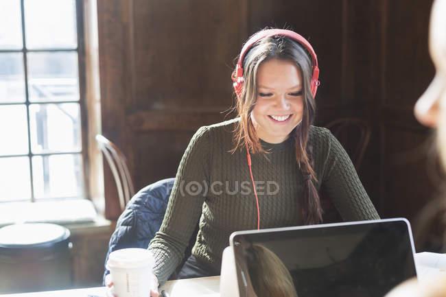 Donna che usando le cuffie, stando seduti nella caffetteria — Foto stock