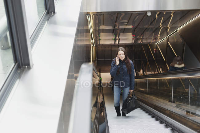 Woman using mobile phone on escalator — Stock Photo