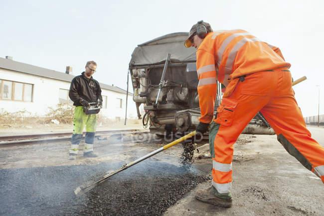 Trabajadores manuales pavimentación en la carretera - foto de stock