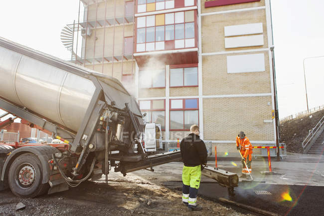 Workers paving at road construction site — Stock Photo