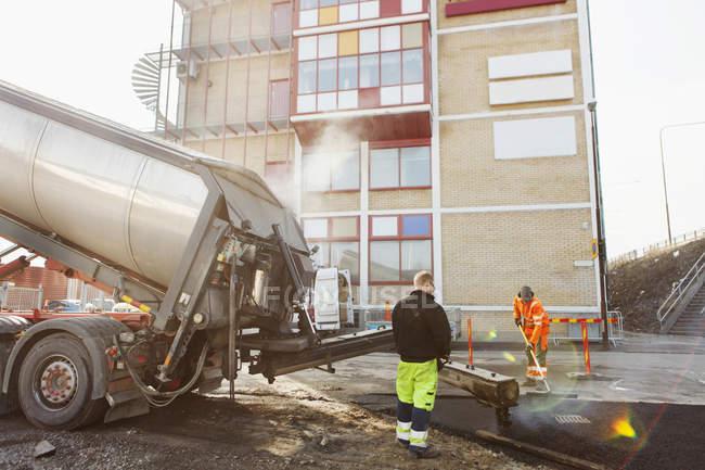 Trabajadores pavimentando en obra viaria - foto de stock