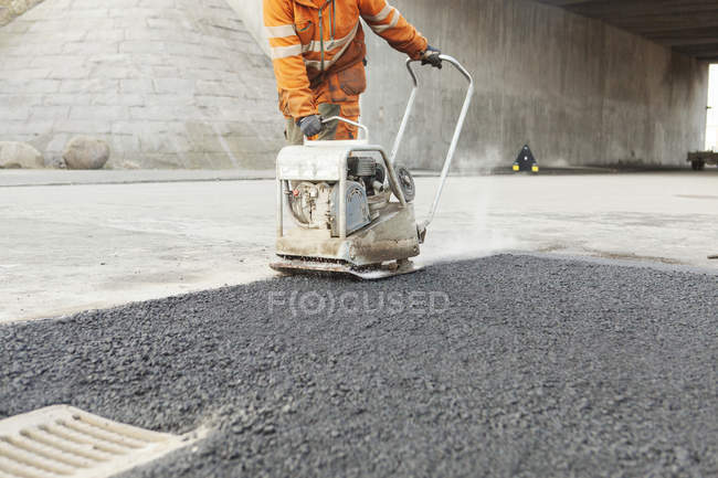 Manual worker laying asphalt — Stock Photo