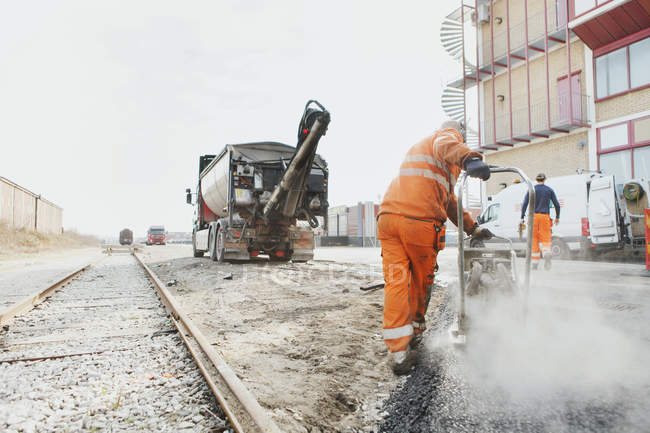 Manual worker laying asphalt — Stock Photo