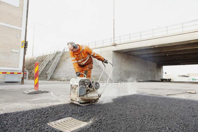 Trabajador manual maduro que pone asfalto - foto de stock