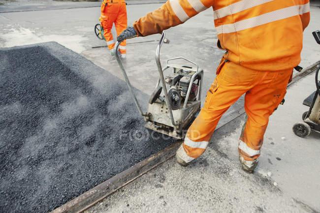 Trabajador manual que pone asfalto - foto de stock