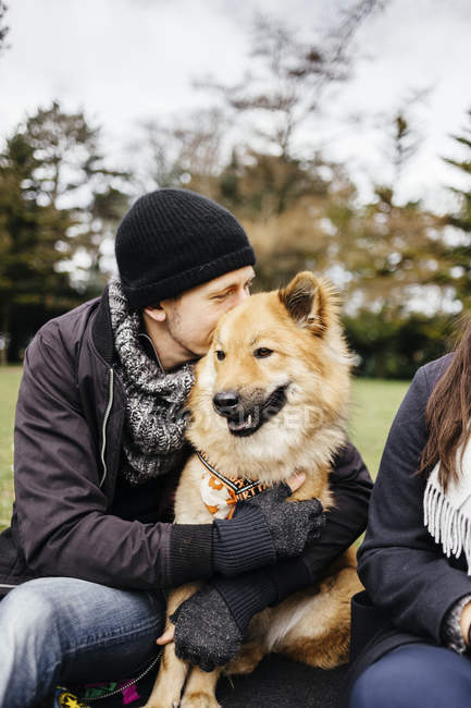 Man embracing Eurasier at park — Stock Photo