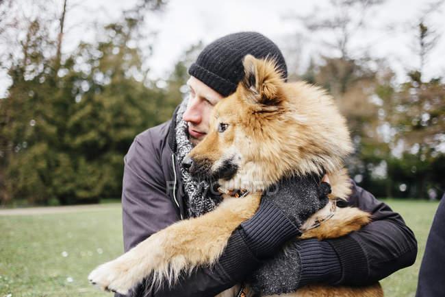 Man embracing Eurasier at park — Stock Photo